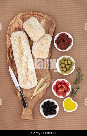 Picnic food and antipasti with olives, sun dried and fresh tomatoes, olive oil, with ciabatta bread on an olive - Stock Photo