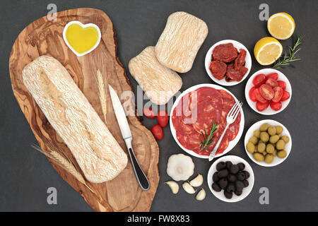 Antipasti with olives, salami, sun dried and fresh tomatoes, garlic, lemon, oil, with ciabatta bread on an olive - Stock Photo