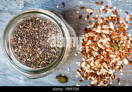 Mixed seeds and a jar of chia seeds - Stock Photo