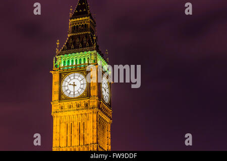 Elizabeth Tower's clock and Big Ben by night on a purple sky. - Stock Photo