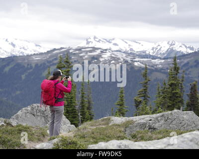 A young female hiker on mountain summit holding a smart phone in Whistler Blackcomb alpine hike, BC, Canada - Stock Photo