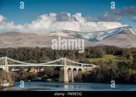 The Menai bridge crossing from Anglesey to the mainland, with the snow spattered Carneddau mountains in the distance. - Stock Photo