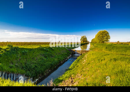 Modern irrigation canal that runs through the cultivated fields of ...