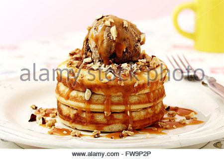 pancakes with ice cream and caramel on kitchen table background - Stock Photo