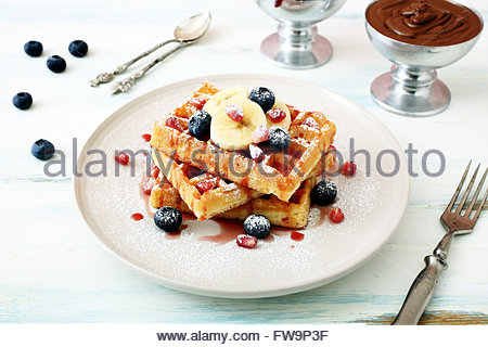 waffles with fresh berries and banana on kitchen table background - Stock Photo