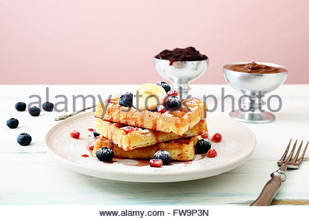 top view Belgian waffles with fresh berries and banana on kitchen table background - Stock Photo