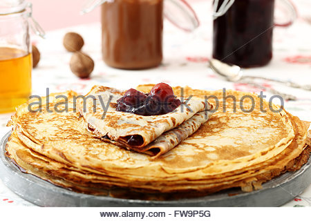 pancakes with berry jam on kitchen table background - Stock Photo