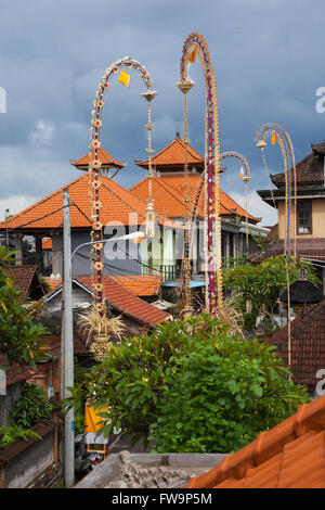 Traditional balinese roofs and ceremonial bamboo decorations on the street during celebrations of Nyepi, Day of - Stock Photo