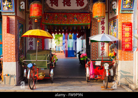 Rickshaw tricycles near the entrance to Hock Teik Cheng Sin Temple, Armenian Street, Penang, Malaysia - Stock Photo
