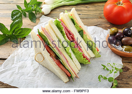 club sandwich with ham and salami on rustic wooden table - Stock Photo