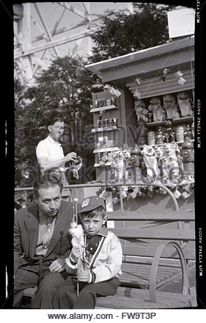 father posing with son on a day outing at a fairground USA 1950s - Stock Photo