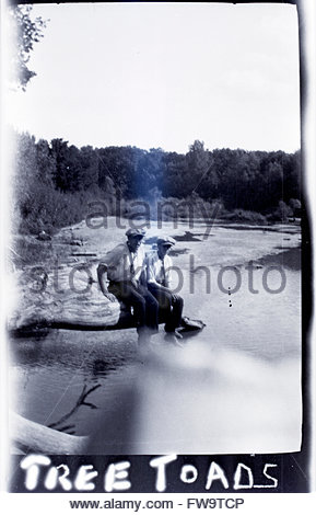 deteriorating photo of two men sitting on rock by water edge 1920s USA - Stock Photo