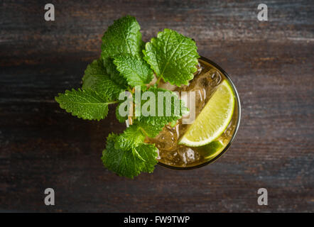 Old fashioned cocktail with lime and mint on the wooden table - Stock Photo