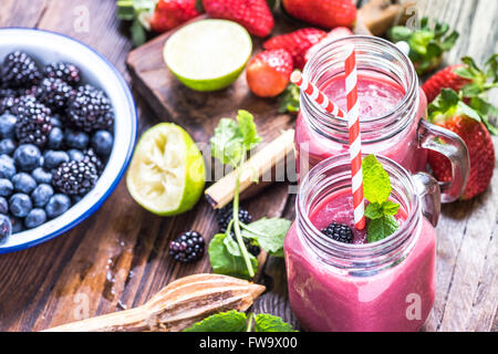 Preparation of antioxidant and refreshing smoothie, well being and weight loos concept. On wooden table from above. - Stock Photo