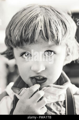portrait of small boy eating looking at camera - Stock Photo