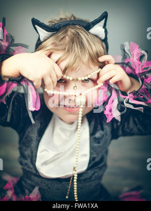 small girl wearing face mask holding pearls - Stock Photo