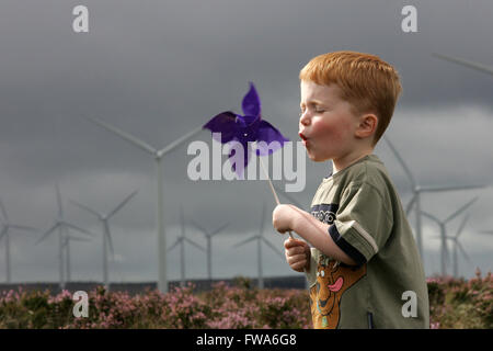 young boy playing with windmill on wind farm - Stock Photo