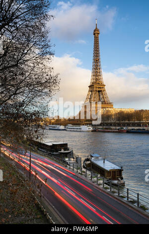 Before sunset at the Eiffel Tower along the Seine River in Paris with car light trails on Voie Georges Pompidou. - Stock Photo