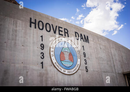 Logo and sign on the side of the Hoover Dam site in southwest United States. - Stock Photo