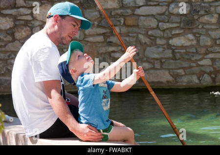 Father and son sitting at the edge of a pool dangling their feet in the water playing with a fishing net - Stock Photo