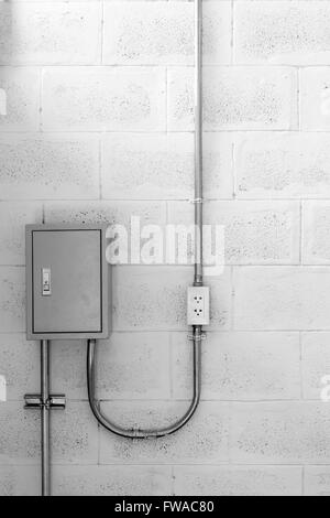 energy electric plug on a concrete wall stock photo royalty electric box on concrete wall steel tube and plug black and white stock