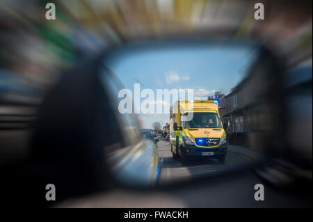 An racing ambulance with flashing lights overtakes a car which sees it in it's wing mirror - Stock Photo