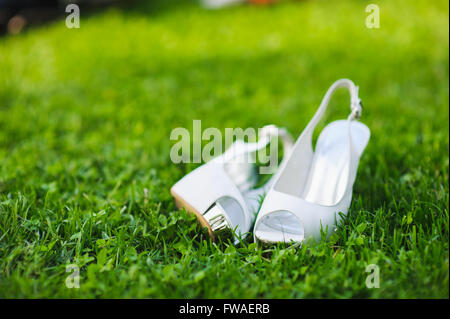 white shoes on green grass bridal white shoes on green lawn. Wedding shoes. - Stock Photo