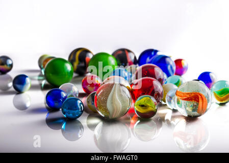 Group of mixed marbles on a reflective white surface - Stock Photo