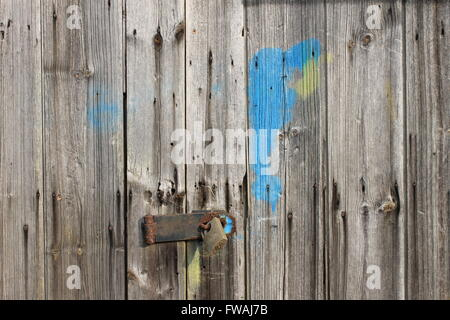 Patch of blue paint and a rusty padlock on an old wooden paneled garage door - Stock Photo