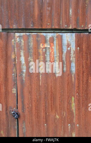 Rusty, corrugated sheet metal shed door and padlock - Stock Photo