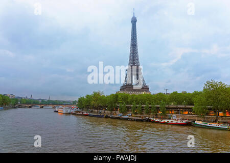 Eiffel Tower and Boats on Seine River in Paris in France, in the evening. Eiffel Tower is an iron lattice tower - Stock Photo