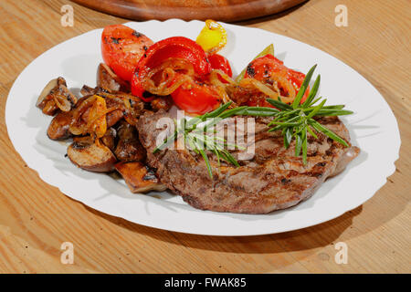 Grilled beef steak with mushrooms, peppers, tomatoes on a plate - Stock Photo