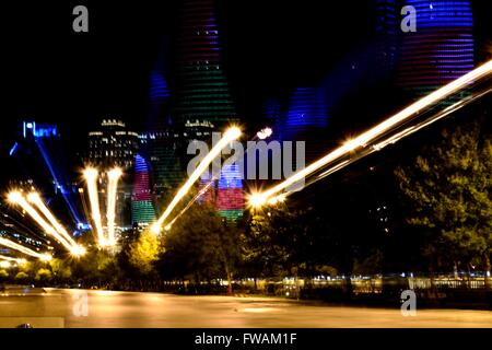 Abstract shot of Flame Towers lit up with colours of Azerbaijani flag. Modern buildings seen from Baku Bulvar, long - Stock Photo