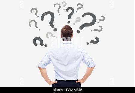 business man looking at the question marks on white board and thinking. - Stock Photo