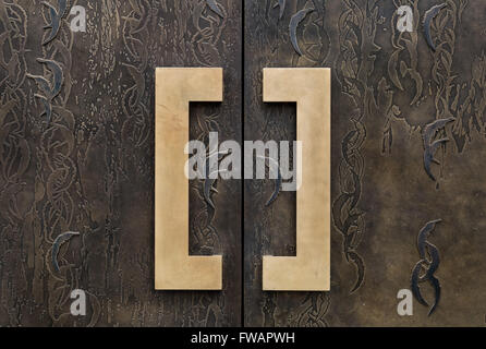 Brass doorhandles on a patterned bronze door on a London apartment - Stock Photo