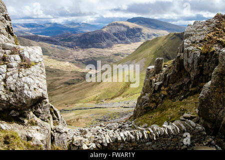 View SE to distant Moel Hebog across Cwm Pennant from Craig Cwm Silyn on Nantlle Ridge in Snowdonia National Park - Stock Photo