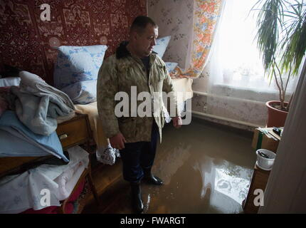 Omsk, Russia. 2nd Apr, 2016. A man in a waterlogged private house. © Dmitry Feoktistov/TASS/Alamy Live News - Stock Photo