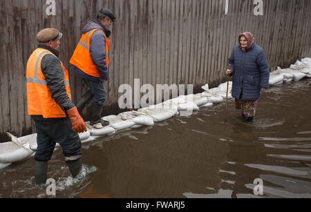 Omsk, Russia. 2nd Apr, 2016. People on a waterlogged street. © Dmitry Feoktistov/TASS/Alamy Live News - Stock Photo
