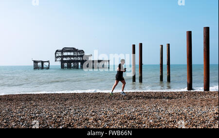 Brighton, UK. 3rd April, 2016. A runner passes by the West Pier early this morning in the warm sunny weather on - Stock Photo