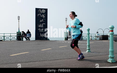 Brighton, UK. 3rd April, 2016. A runner passes by the Kissing sculpture early this morning in the warm sunny weather - Stock Photo