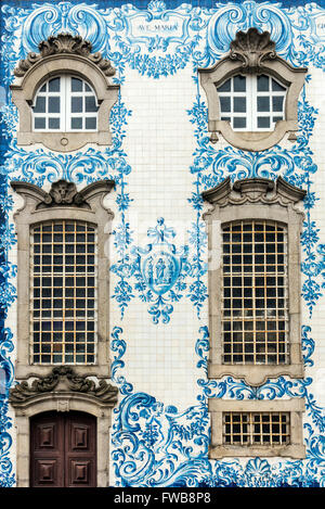 Traditional azulejos hand-painted tiles covering the exterior wall of the Igreja dos Carmelitas church in Porto, - Stock Photo
