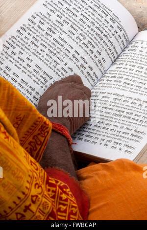 Nepal, Pashupatinath.  Hindu Sadhu (Ascetic) Reading Hindu Scriptures. - Stock Photo