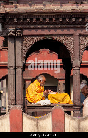 Pashupatinath, Nepal.  Sadhu, a Hindu Ascetic or Holy Man, Reading Sacred Texts in the Temple. - Stock Photo