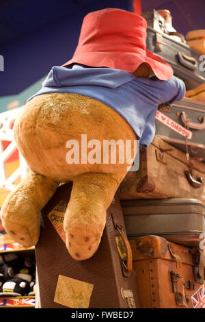 Paddington Bear soft toy climbing on suitcases - Stock Photo