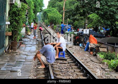 Men crouching on the railway tracks in Hanoi, Vietnam, Asia - Stock Photo