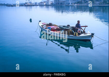 A fisherman in his boat in the harbour at Nafplion in Greece. - Stock Photo
