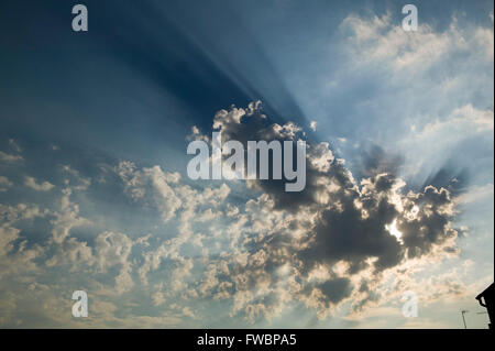 Large clouds block out the sun sending huge rays of light spilling out from around the edges. - Stock Photo