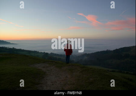 A young girl standing on top of a hill watching as the sun sets and the mist gathers in the valley below. - Stock Photo