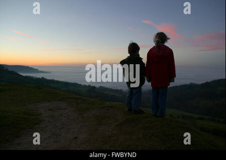 Two young children standing on a hill top watching the sunset as night falls and the mist gathers in the valley - Stock Photo
