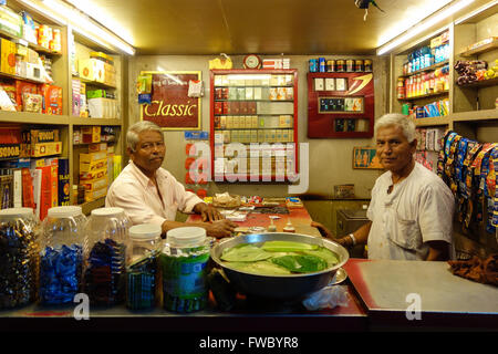 Two elderly Indian shopkeepers pose inside their shop selling tobacco products in Vadodara, Gujarat, India. - Stock Photo